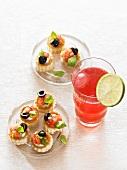 Häppchen mit Tomaten und Oliven, ein Glas Campari Cocktail