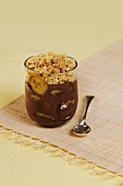 Chocolate cream with bananas and crumble in glass