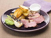 Slices of roast lamb with roasted potatoes, garlic & pea puree