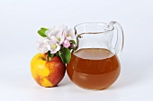 A jug of cider vinegar with apple and apple blossom