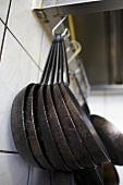 Iron frying pans hanging on a hook in a kitchen