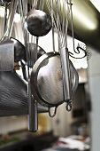 Various kitchen tools hanging on hooks in a kitchen