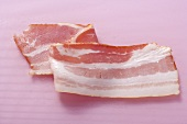 A rasher of bacon on pink background