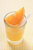 Orange juice with wedge of orange and straw