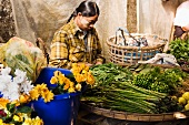 Woman at a flower and vegetable market in Burma