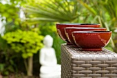 Three red painted bowls from the Burma in an oriental garden