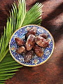 Dates on plate and palm leaf