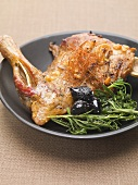 Duck leg with herbs, olives and pine nuts