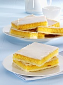 Several pieces of iced orange cake