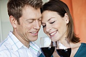 Courting couple clinking glasses of red wine