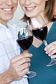 Smiling couple clinking glasses of red wine