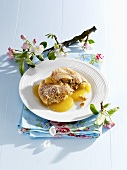 Apple pudding on plate surrounded by apple blossom