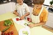 Two boys slicing vegetables