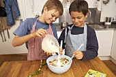 Two boys making pasta salad