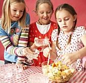 Three girls eating fruit salad