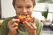 Boy eating home-made pizza