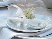 Plastic cutlery with porcelain spoon and wild carrot blossom