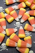 Candy corn on patterned background (skulls and crossbones)
