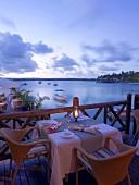 Gedeckter Tisch auf Terrasse auf Mauritius bei Dämmerung