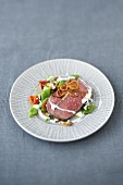 Sliced roast beef on bean salad with horseradish sauce