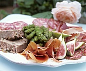 Antipasti plate with ham, figs, asparagus and terrine