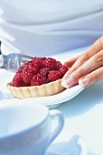 Woman eating a raspberry tartlet