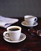 Two cups of coffee and newspaper