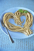Cooked spaghetti arranged in the shape of a heart