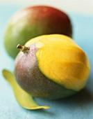 Two mangos, one partly peeled