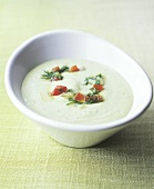 Avocado cream soup with pieces of tomato and dill