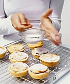 Dusting mince pies with icing sugar