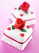 Two iced petit fours with marzipan roses and tiny hearts