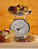 Apples on kitchen scales, apple slices, cinnamon & sugar in front