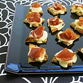 Warm canapés with Vacherin cheese and prosciutto