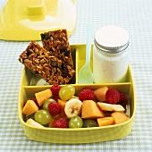 Packed breakfast: muesli bars, yoghurt and fruit salad