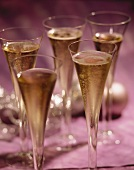 Five champagne flutes, Christmas baubles in background