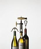 Three wine bottles with corkscrews