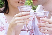 Man and woman clinking glasses of rosé wine (close-up)