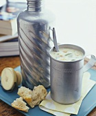 Vegetables soup in Thermos flask and mug, baguette