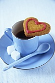 Heart-shaped biscuit and a cup of coffee