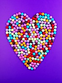 Chocolate beans forming heart on purple background