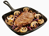 Beef steak with onions and mushrooms in a grill pan