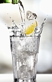 Wasser mit Zitronenschnitz in ein Glas gießen
