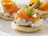 Blinis topped with soft cheese, smoked salmon and rocket