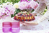 Woman putting summer berry torte on garden table