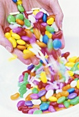 Coloured sweets falling out of someone's hands