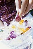 Hand nimmt Fruchtbonbon aus einem Schälchen