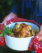 Chicken with rosemary, vegetables and lemon in a cocotte