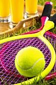 Children's tennis rackets & ball in grass, orange juice behind