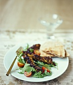 Kala murgi - blackened Indian chicken sticks on bed of salad